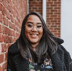 A woman with long brown hear, wearing glasses, a black jacket, and a floral black shirt, smiles in front of a brick wall.