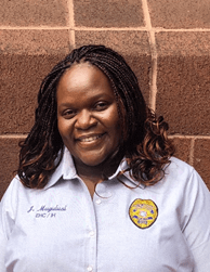 A woman with her hair in braids, wearing a blue button down with a badge, smiles in front of a brick wall.