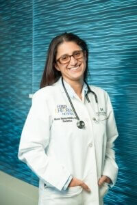 A woman with long brown hair, wearing glasses, a lab coat and stethoscope, stands in front of a turquoise wall and smiles at the camera with her hands in her pockets
